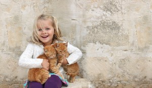 little girl holding two orange kittens